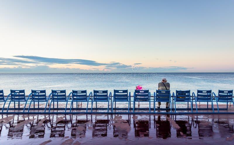 Uomo che si siede sulla sedia accanto al mare di Nizza, Francia fotografia stock libera da diritti