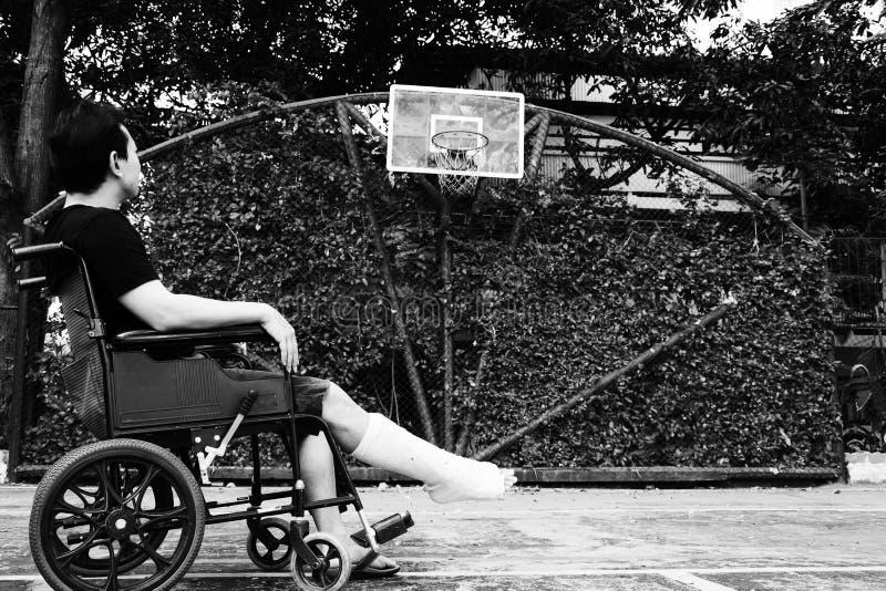 Uomo che si siede sulla sedia a rotelle con la gamba rotta immagini stock