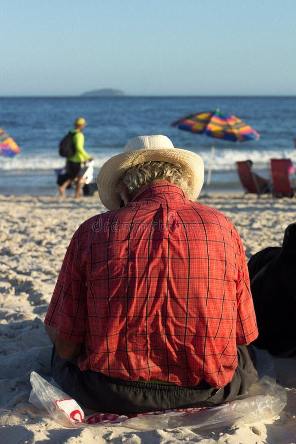 uomo che si siede sulla spiaggia del copacabana immagini stock