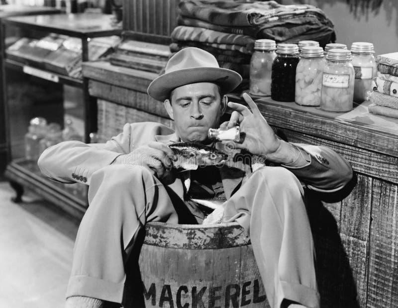Uomo che si siede in un barilotto ed in un sale di versamento su un pesce (tutte le persone rappresentate non sono vivente più lu immagini stock