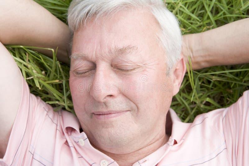 Uomo che si trova nel sonno dell'erba fotografie stock