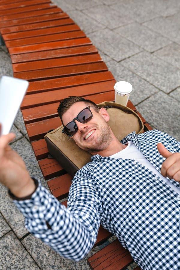 Uomo che si trova su un banco di parco che fa selfie con il cellulare fotografia stock libera da diritti