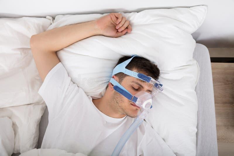 Uomo che si trova sul letto con l'apnea di sonno e la macchina di CPAP immagini stock