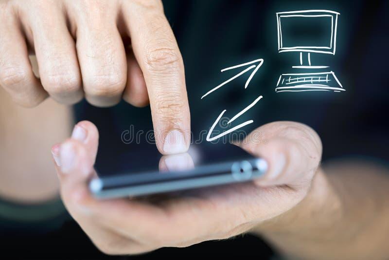 Uomo che sincronizza il suoi cellulare e desktop fotografie stock