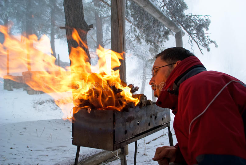 Uomo che smazza fuoco in griglia fotografia stock