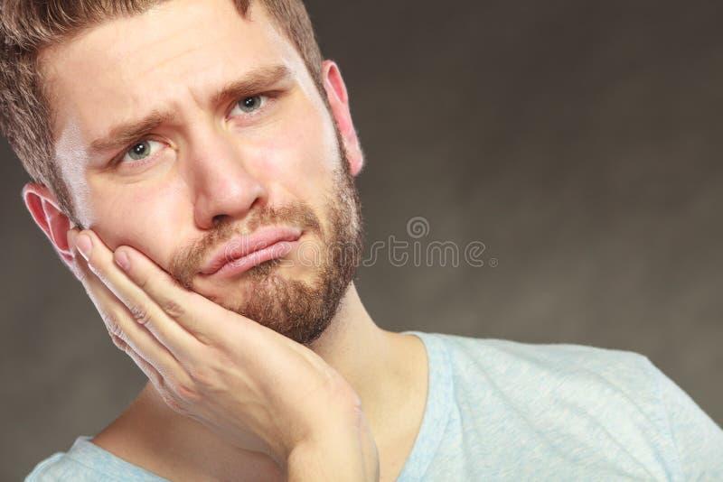 Uomo che soffre dal dolore di dente di mal di denti fotografia stock libera da diritti
