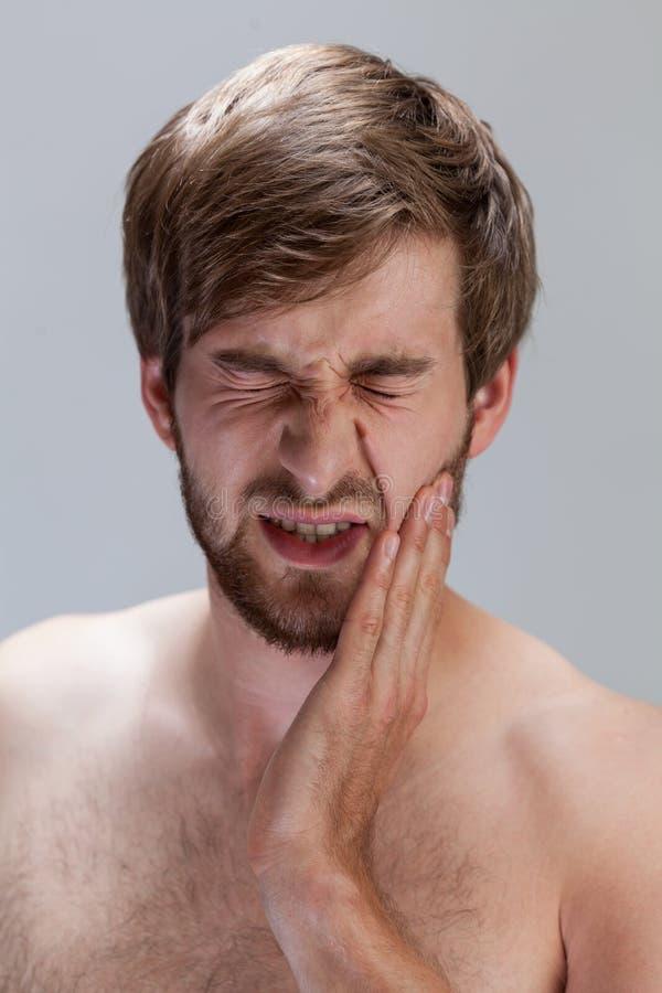 Uomo che soffre dal mal di denti immagini stock