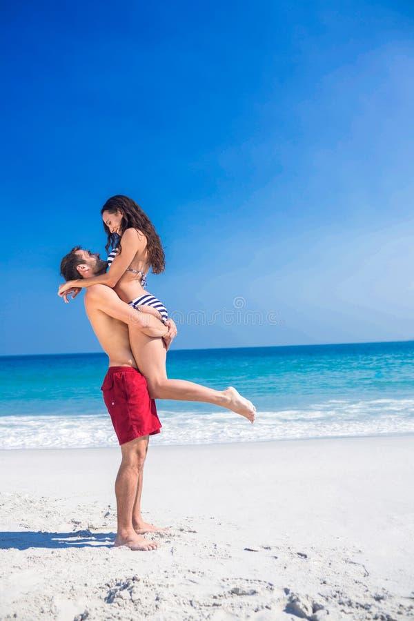Uomo che solleva la sua amica alla spiaggia immagine stock libera da diritti