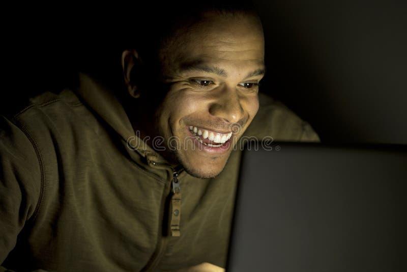 Uomo che sorride al suo computer portatile alla notte fotografie stock libere da diritti