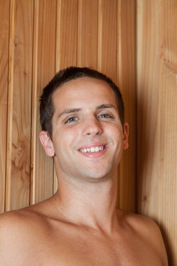Uomo che sorride dentro la sauna fotografia stock libera da diritti