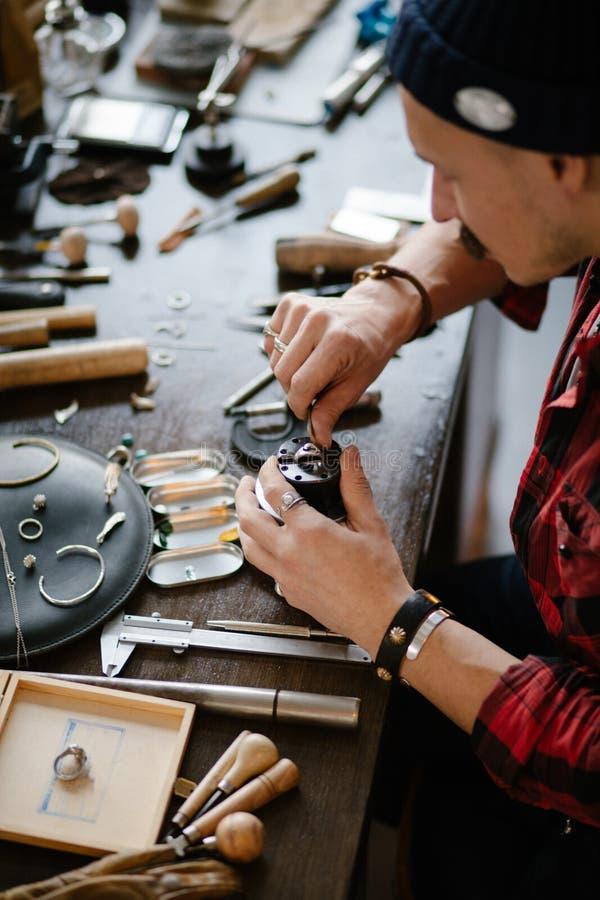 Uomo che sostituisce il gioiello mentre sedendosi alla tavola nell'officina immagini stock libere da diritti