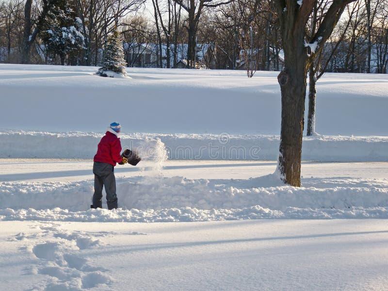 Uomo che spala neve fotografie stock
