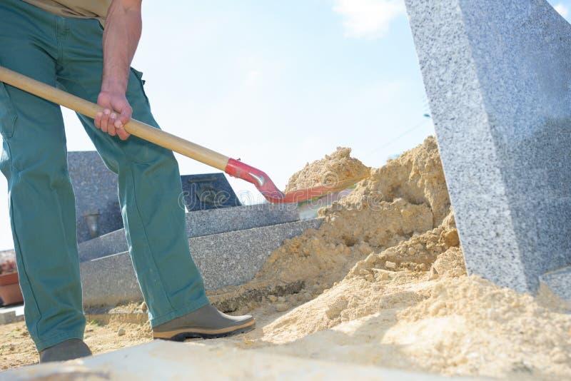 Uomo che spala sabbia in cimitero fotografia stock