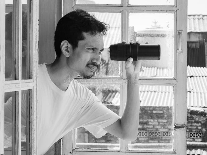 Uomo che spia facendo uso del teleobiettivo immagini stock