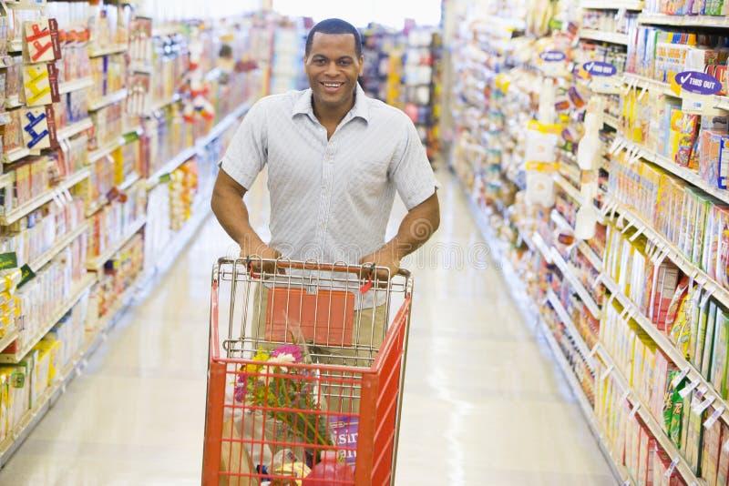Uomo che spinge carrello lungo la navata laterale del supermercato fotografia stock