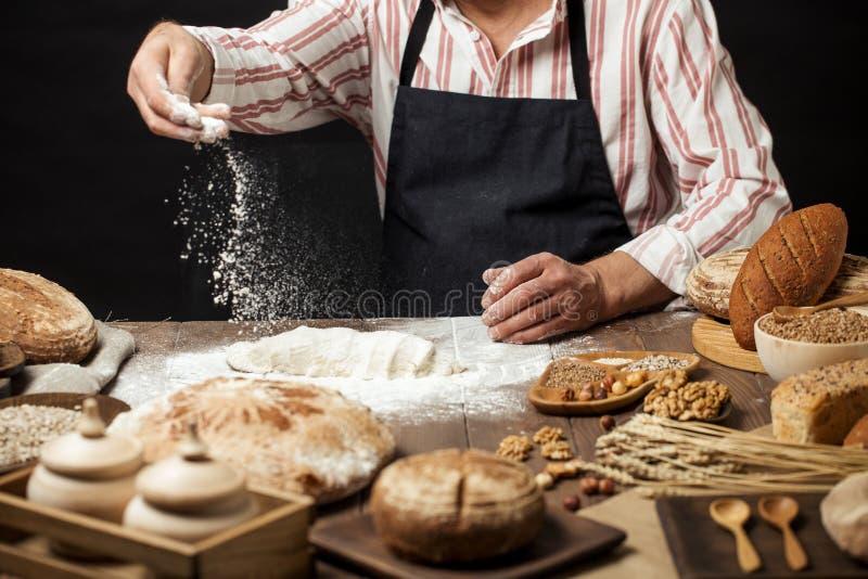 Uomo che spruzza una certa farina su pasta Mani che impastano pasta, vista potata immagine stock