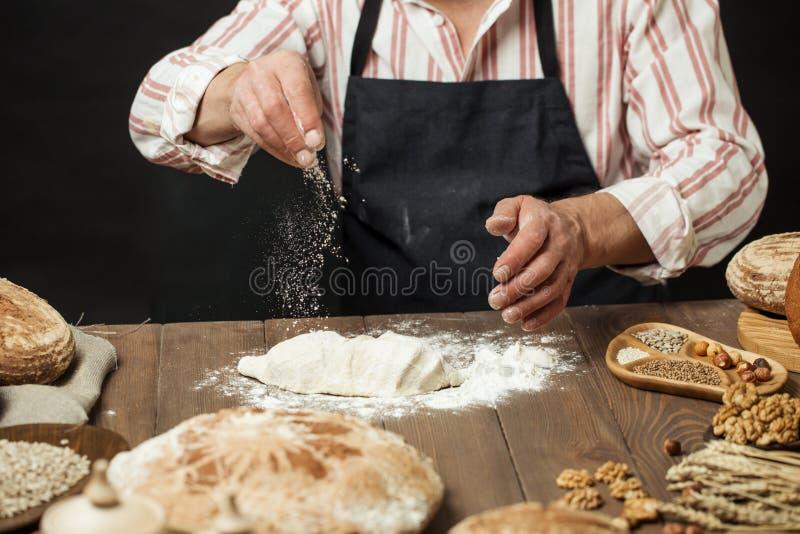 Uomo che spruzza una certa farina su pasta Mani che impastano pasta, vista potata immagine stock libera da diritti