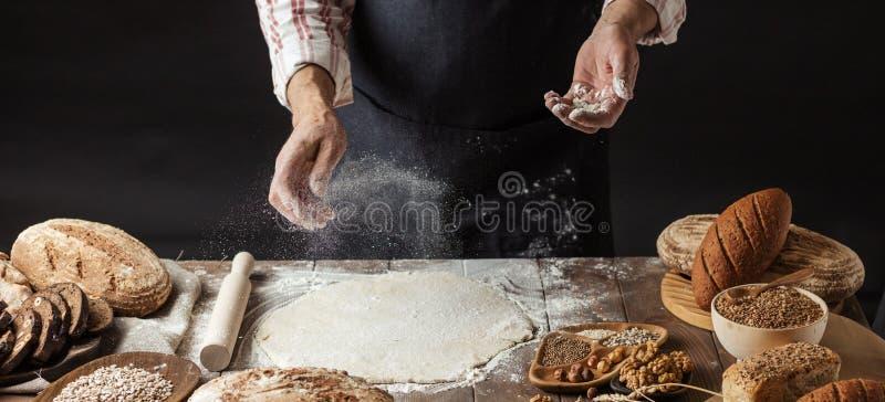 Uomo che spruzza una certa farina su pasta Mani che impastano pasta, vista potata immagini stock libere da diritti