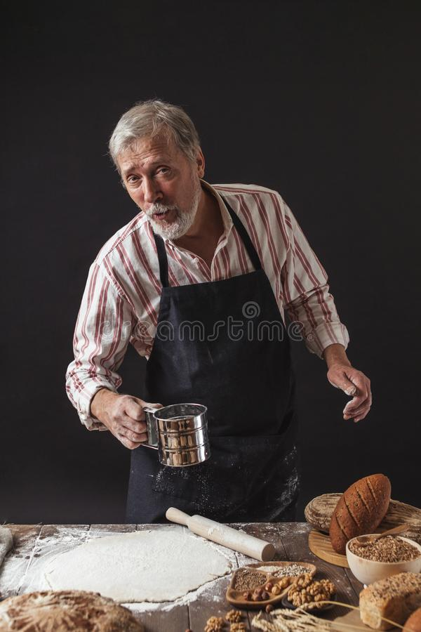 Uomo che spruzza una certa farina su pasta Mani che impastano pasta, vista potata fotografia stock