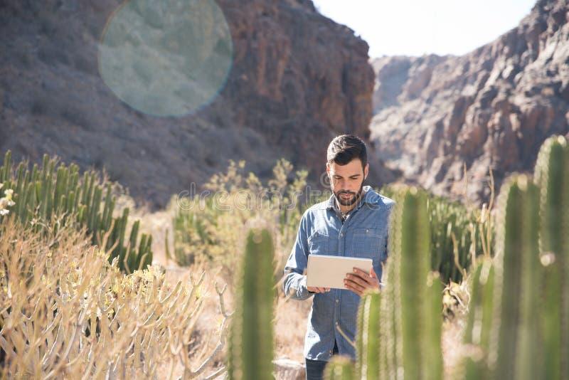Uomo che sta accanto ad un cactus che guarda giù fotografia stock libera da diritti