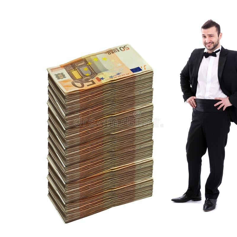 Uomo che sta accanto alla pila enorme di soldi fotografia stock