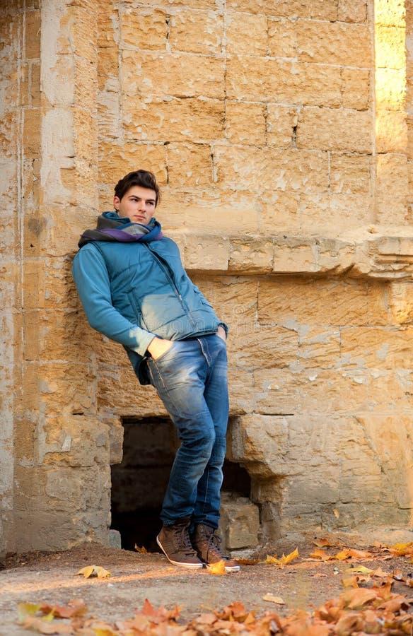 Uomo che sta contro il muro di mattoni di lerciume fotografia stock libera da diritti