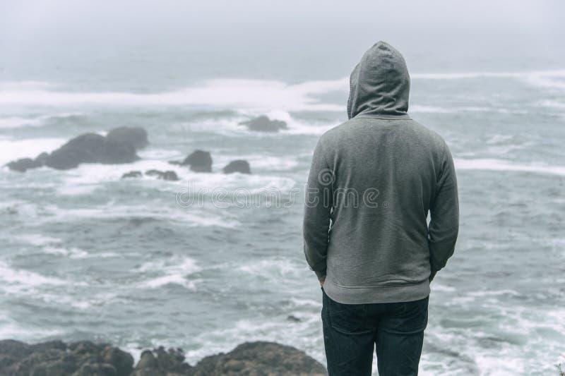 Uomo che sta davanti all'oceano Pacifico fotografia stock libera da diritti