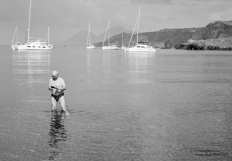 Uomo che sta nel mare che esamina telefono cellulare immagini stock