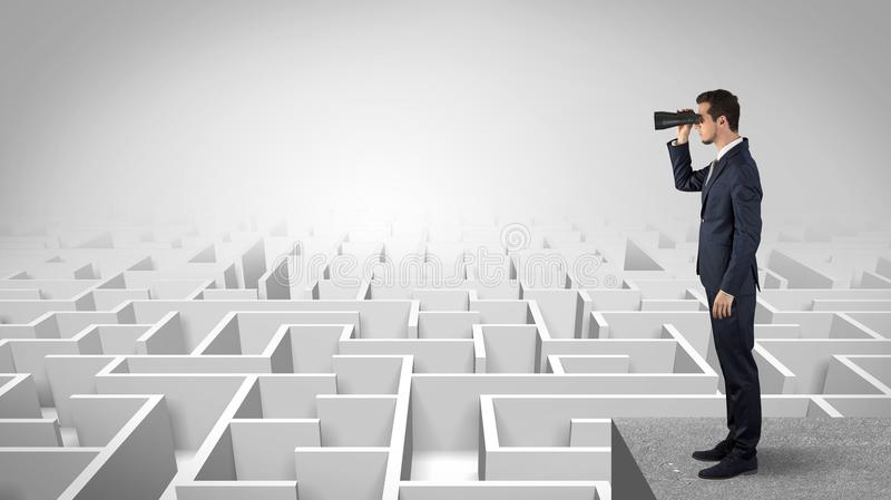Uomo che sta sopra un labirinto con il binocolo immagine stock libera da diritti