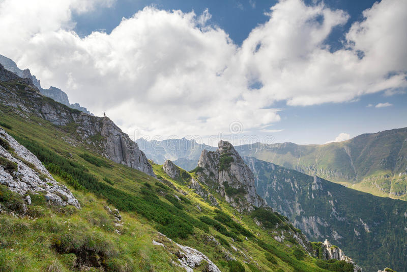 Uomo che sta su un picco di montagna fotografia stock libera da diritti