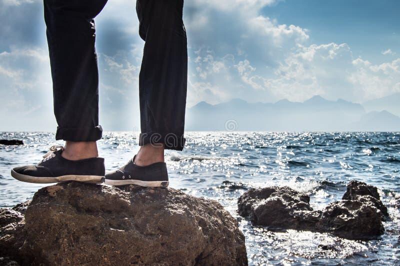 Uomo che sta su una roccia immagini stock libere da diritti