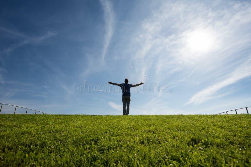 Uomo che sta sull'erba al sole fotografia stock