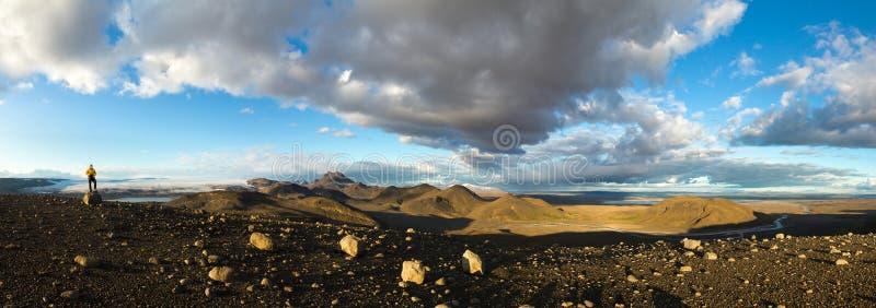 Uomo che sta sulla roccia della montagna nel panorama illuminato drammatico del paesaggio in Islanda Bello paesaggio del sole di  fotografie stock libere da diritti