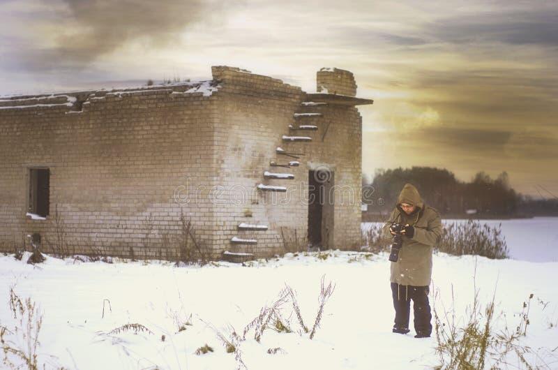 Uomo che sta vicino alla costruzione sovietica abbandonata immagine stock