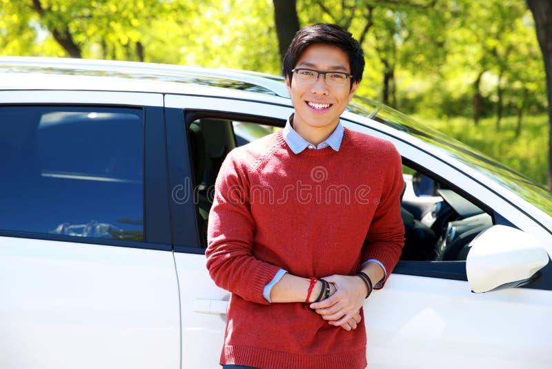 Uomo che sta vicino alla sua automobile in parco immagine stock