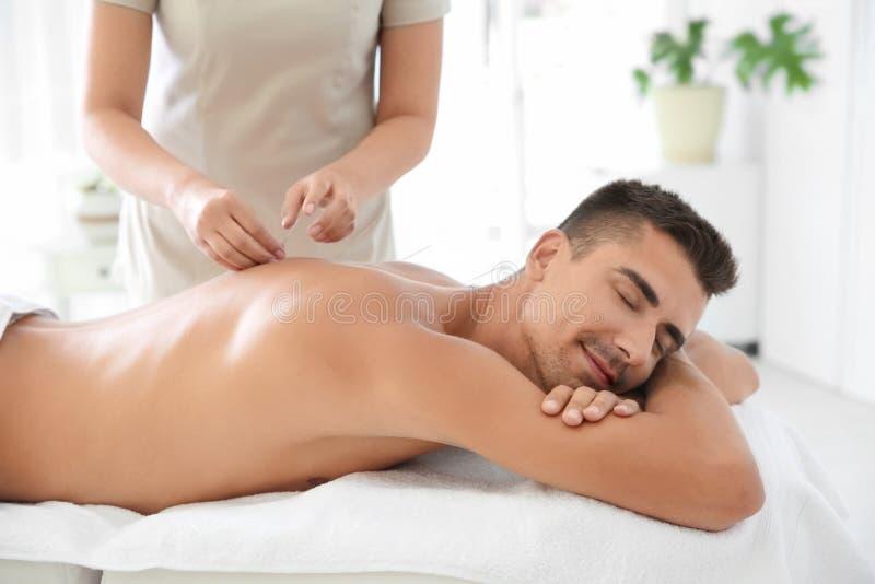 Uomo che subisce trattamento di agopuntura in salone fotografie stock