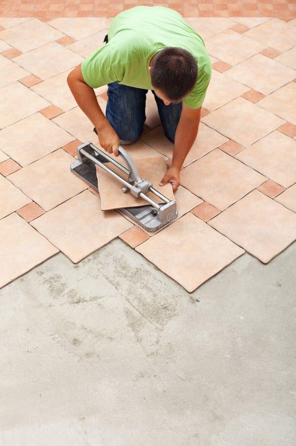 Uomo che taglia le piastrelle per pavimento ceramiche con la taglierina manuale fotografia stock