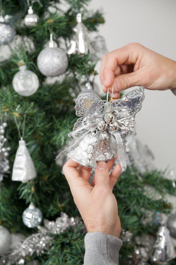 Uomo che tiene Belhi d'argento in Front Of Christmas fotografia stock libera da diritti