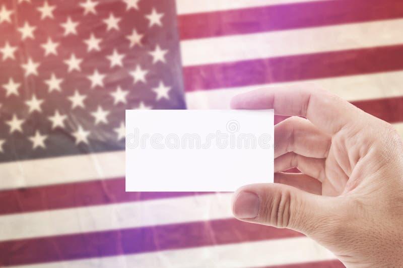 Uomo che tiene biglietto da visita in bianco contro la bandiera nazionale di U.S.A. fotografia stock