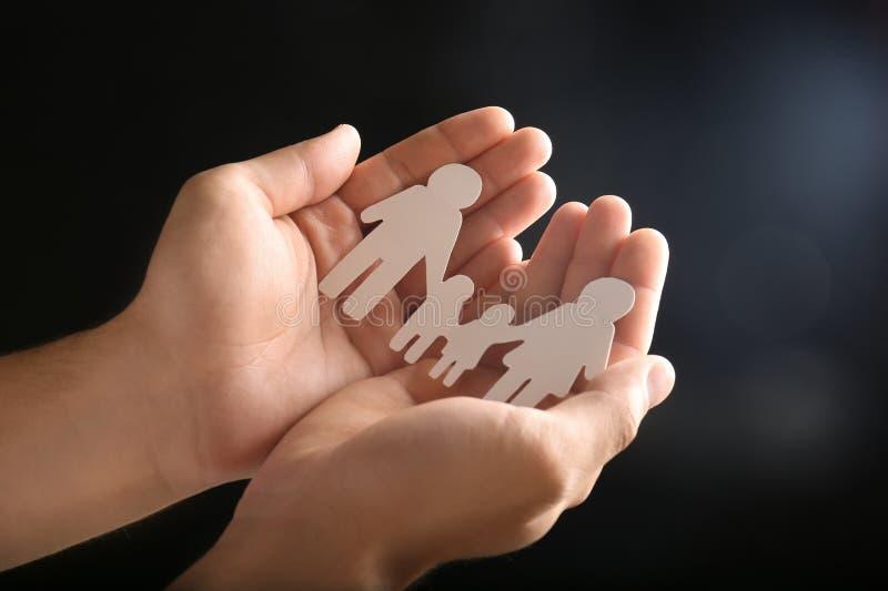 Uomo che tiene carta della famiglia in mani su fondo scuro, primo piano fotografie stock