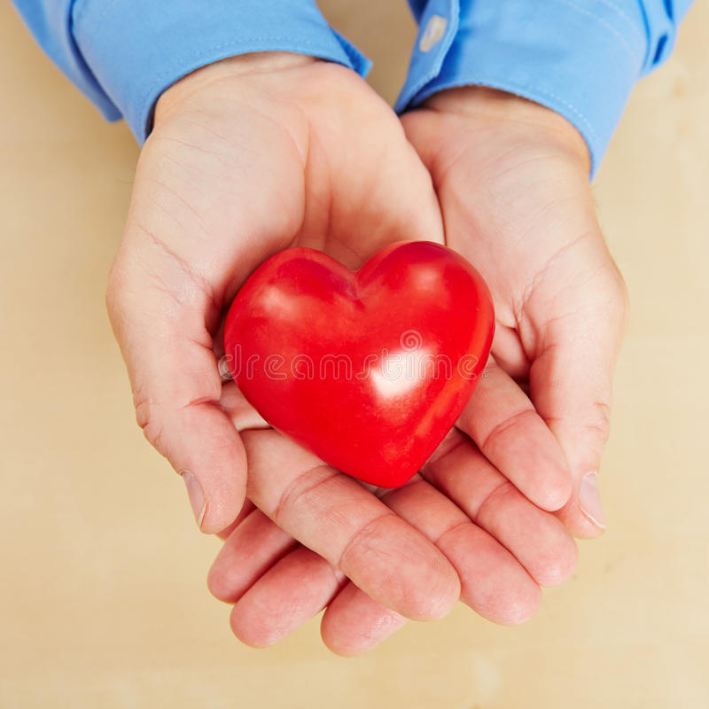 Uomo che tiene cuore rosso in sue mani fotografia stock libera da diritti
