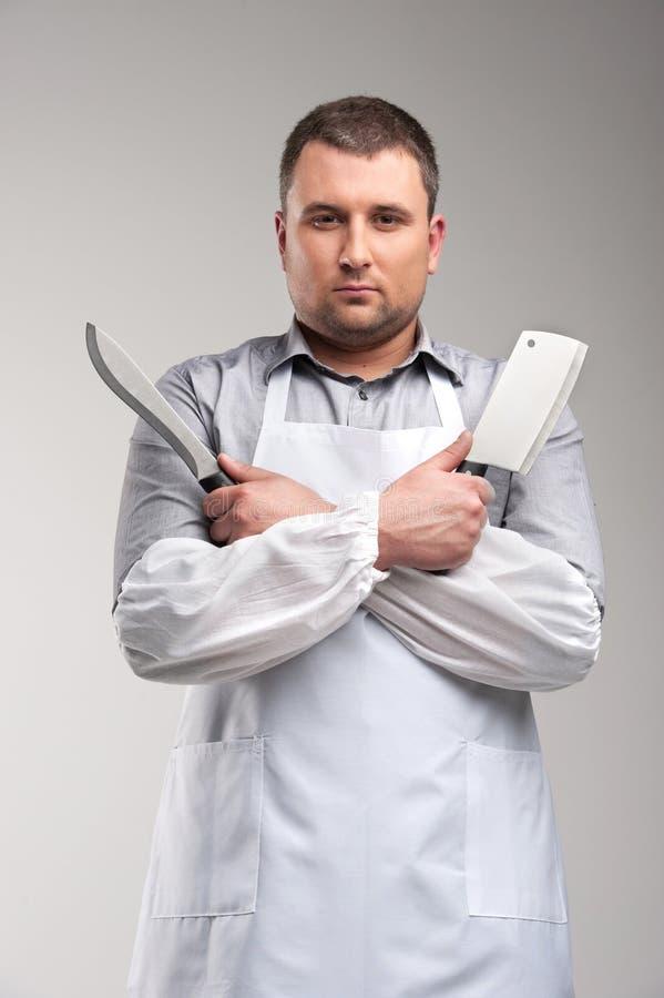 uomo che tiene due coltelli di macellaio immagine stock