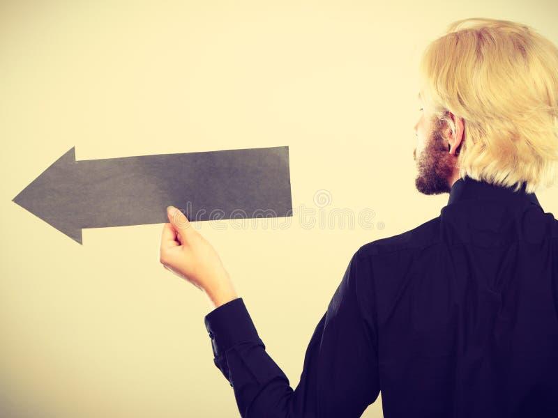 Uomo che tiene freccia nera che indica a sinistra immagini stock libere da diritti