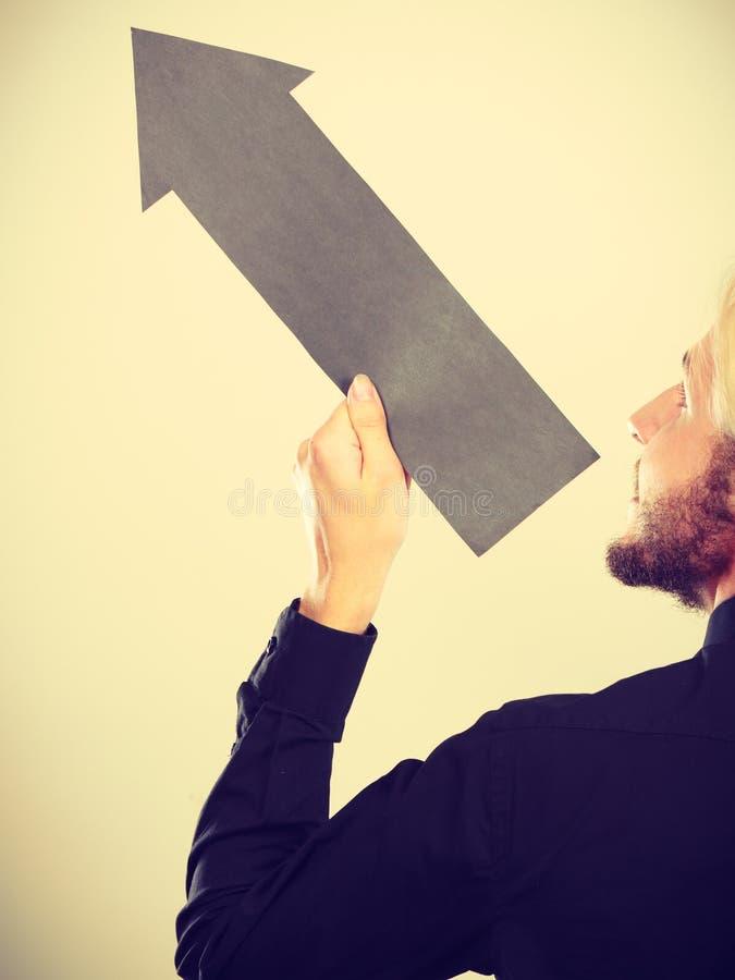 Uomo che tiene freccia nera che indica a sinistra su fotografia stock