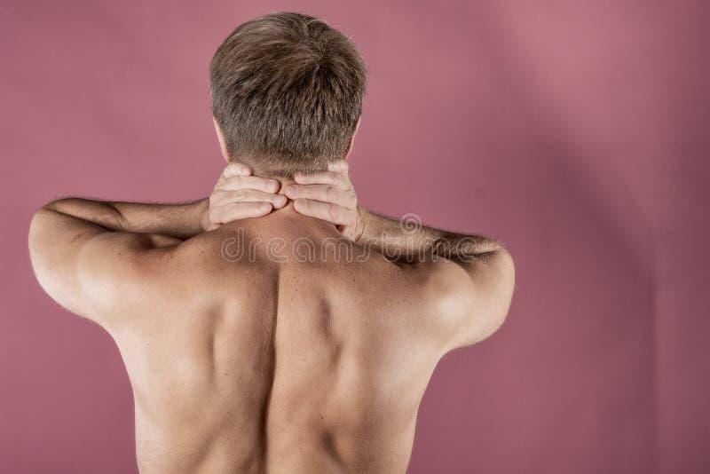 Uomo che tiene il suo collo con entrambe le mani, isolate su fondo rosa Dolore al collo più basso Uomo senza camicia che tocca il fotografia stock libera da diritti