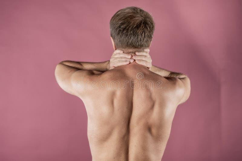 Uomo che tiene il suo collo con entrambe le mani, isolate su fondo rosa Dolore al collo più basso Uomo senza camicia che tocca il fotografia stock