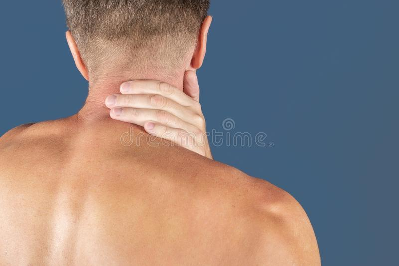 Uomo che tiene il suo collo nel dolore, isolato su fondo blu Dolore al collo più basso Uomo senza camicia che tocca il suo collo  fotografia stock
