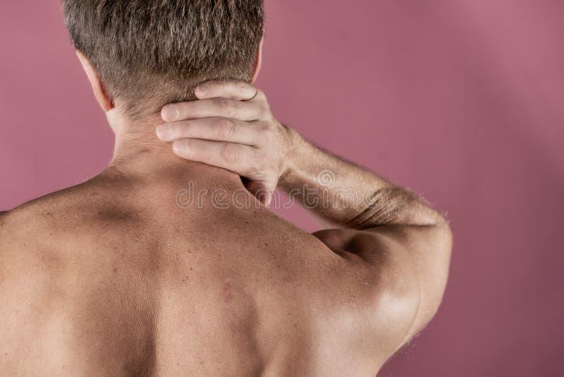 Uomo che tiene il suo collo nel dolore, isolato su fondo rosa Dolore al collo più basso Uomo senza camicia che tocca il suo collo fotografia stock