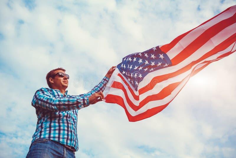 Uomo che tiene la bandiera di U.S.A. Celebrazione della festa dell'indipendenza dell'America 4 luglio immagine stock libera da diritti