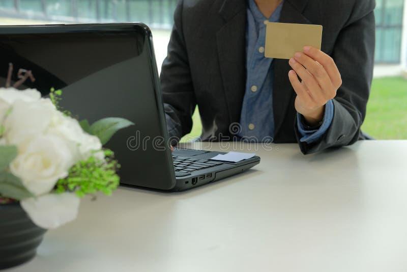 uomo che tiene la carta di credito facendo uso del computer per acquisto online Busi fotografia stock